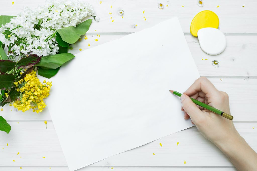 A blank page on a white table next to a bouquet of white and yellow flowers. A person is holding a green pencil, prepared to start writing.