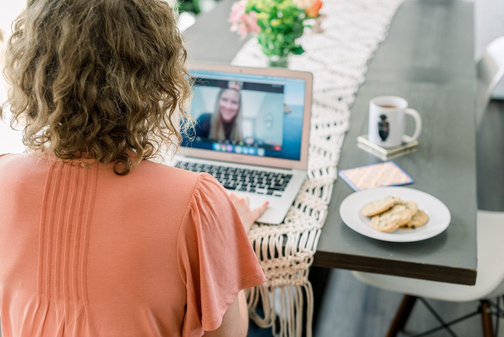 a woman with her back to the camera, having a video chat conversation on her laptop