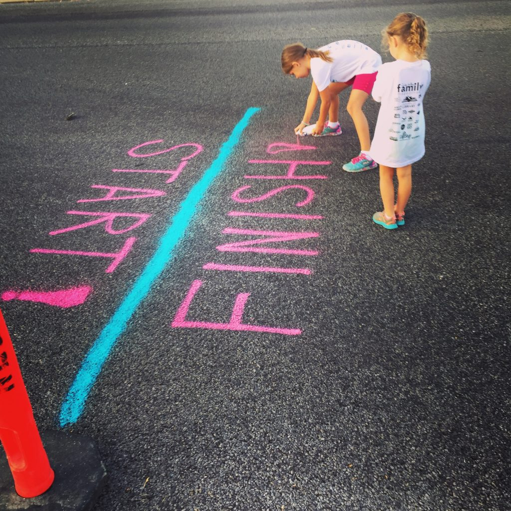 two young girls marking the starting and finishing line for a 5k race in chalk