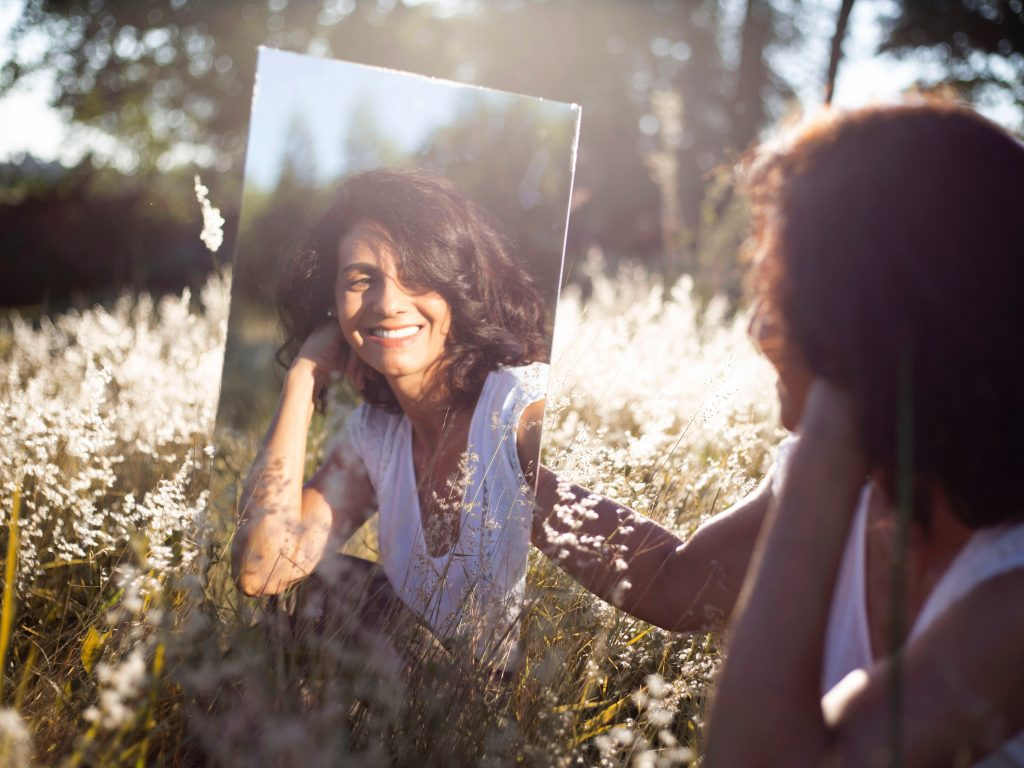 A woman in a sunny field smiling at herself in a mirror