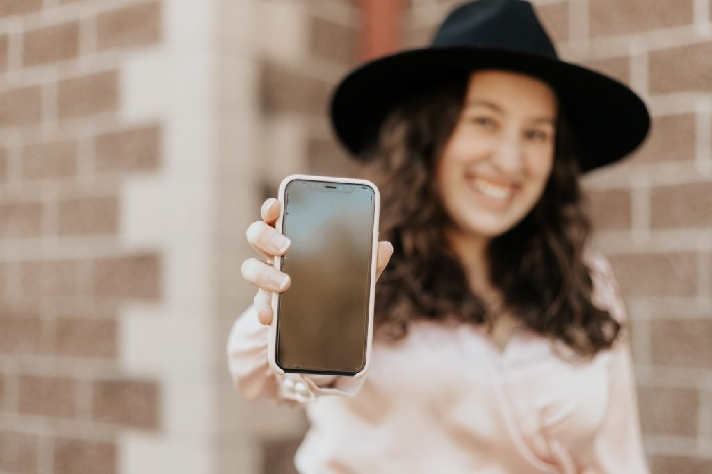 a woman in soft focus, wearing a brimmed hat, holding her phone out in front of her