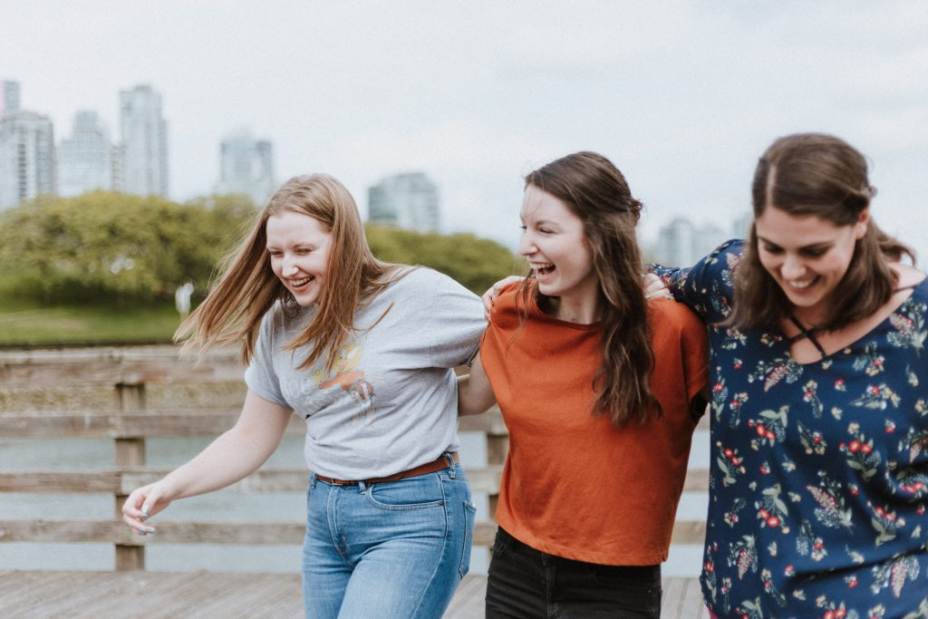 three young women with their arms around each other, smiling and laughing