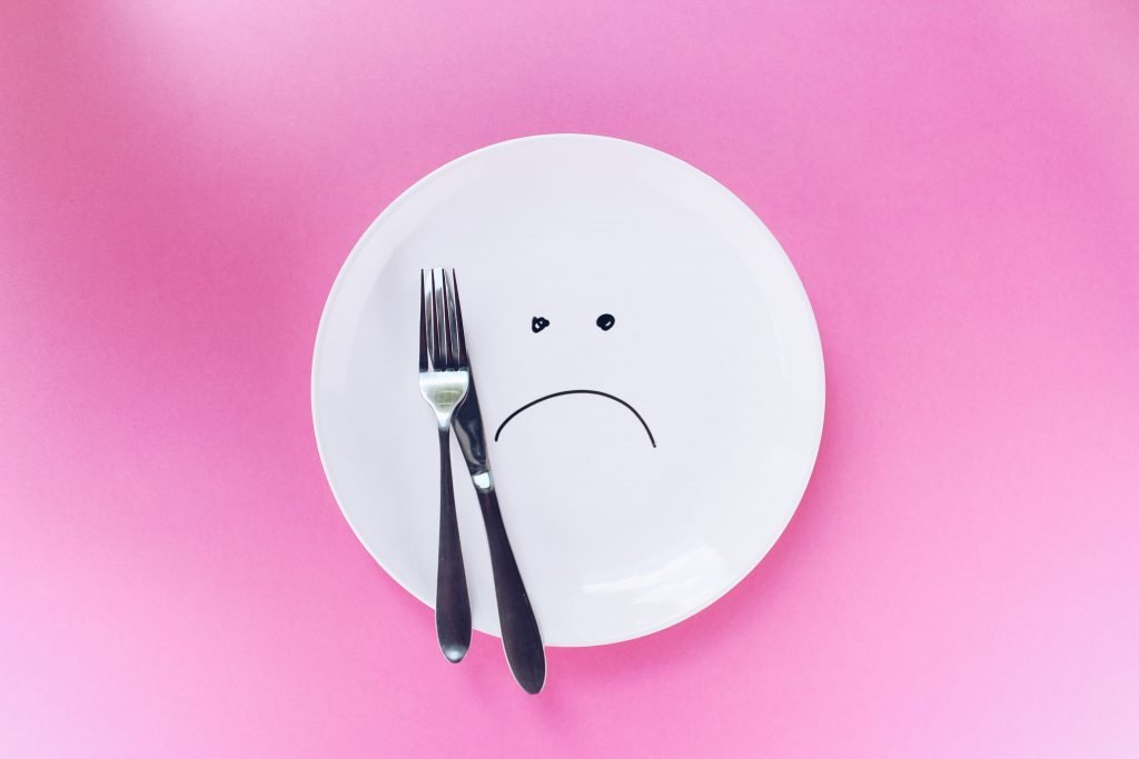 a white plate on a pink background with a sad face drawn on with a sharpie marker