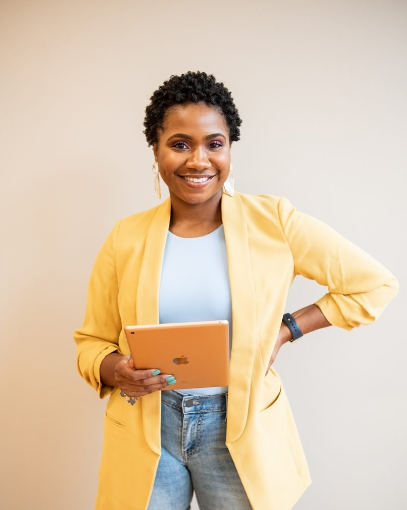 A woman in a sunny yellow blazer and jeans holding an ipad